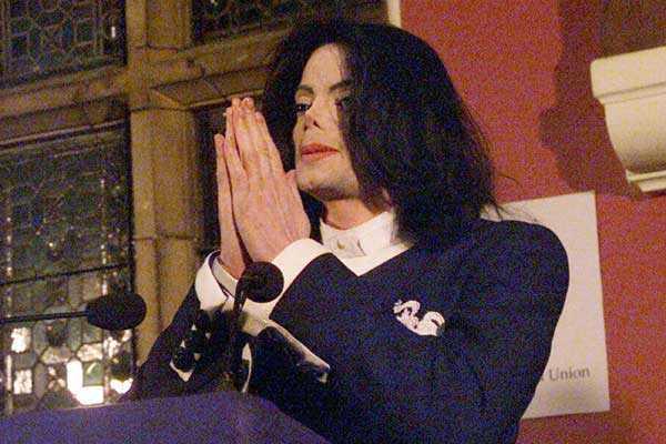 Vemos a un famoso cantante arrodillado con sus manos puestas en actitud de oración