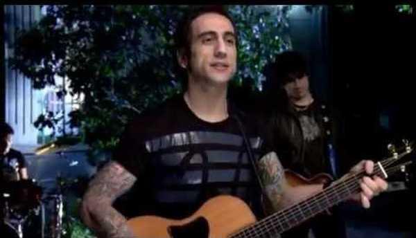 Vemos a un joven con camiseta negra tocando guitarra con su banda