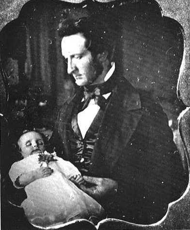 Tenemos aun hombre con traje de época que sostiene un bebe muy elegante dormido