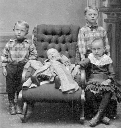 Observamos a tres niños muy bien vestidos que cuidan a un ñiño que duerme en una silla