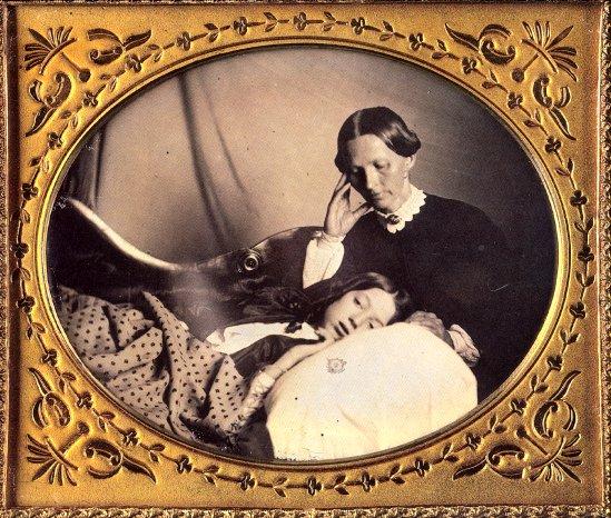 Una mujer con cara triste mira a una niña que duerme