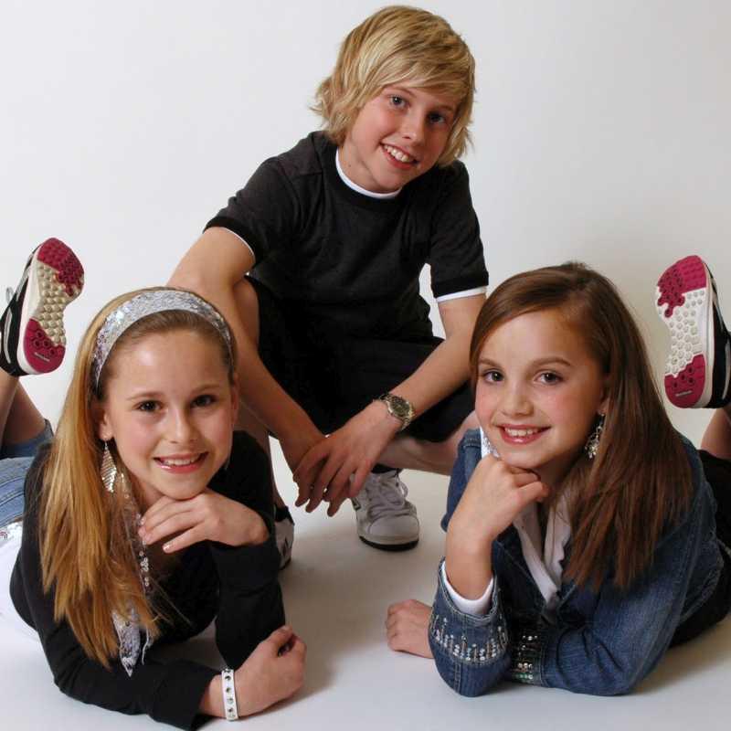 Vemos a tres muy jóvenes con pelo rubio acostados en el suelo sonriendo muy felices