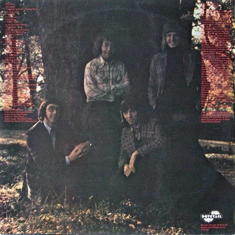 Cuatro hombres en un árbol gigantes con letras rojas pequeñas a los laterales