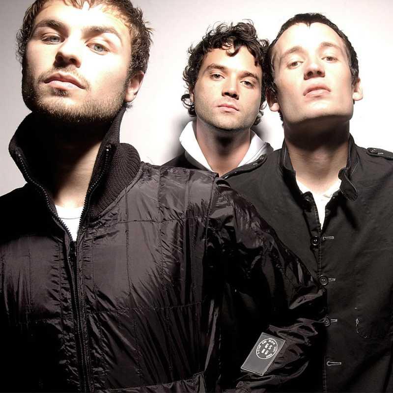 Vemos a tres jóvenes con pelo corto y chaquetas negras con caras serias