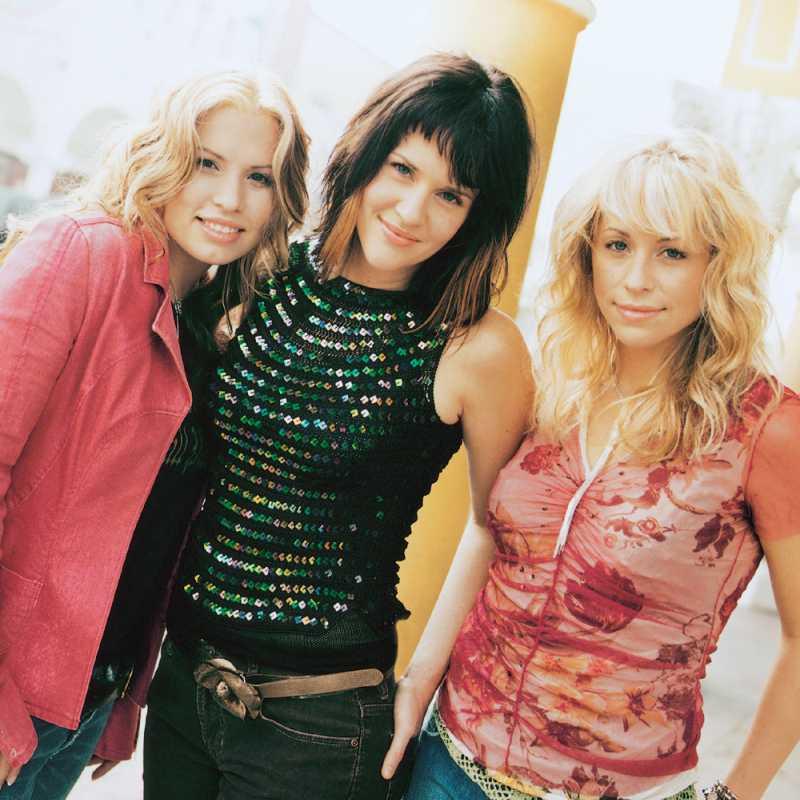 Tenemos acá  tres mujeres muy jóvenes con ropa festiva que miran sonriendo