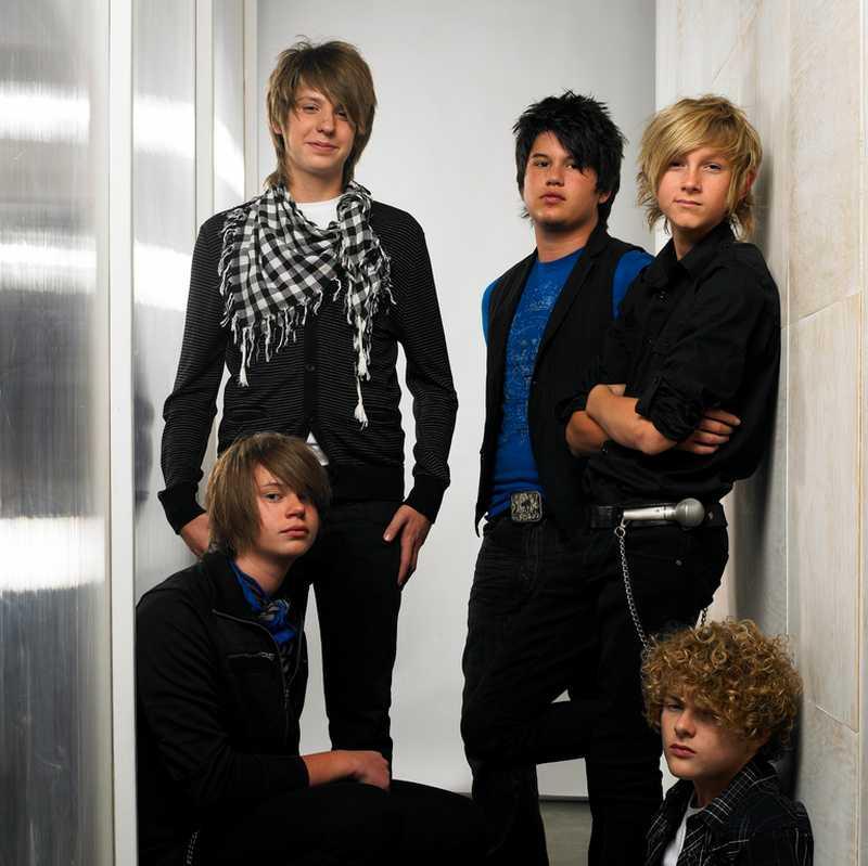 Vemos a un grupo de cinco chicos con ropa oscura que sonríen a la cámara