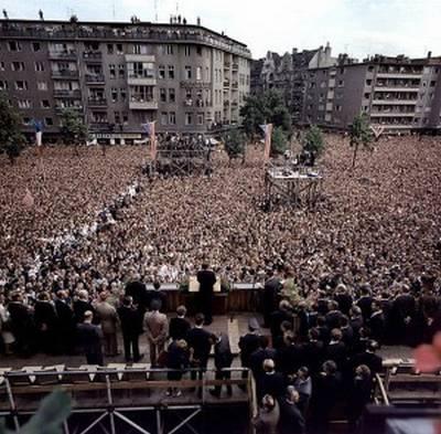 Tenemos un gran multitud y un estrado donde un hombre se dirije a la multitud