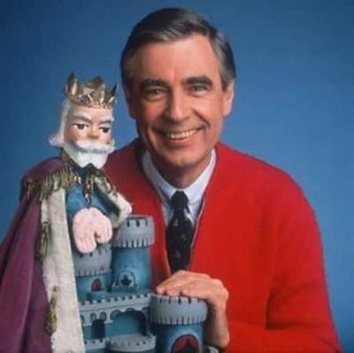 Vemos aun hombre con saco rojo y sonriendo que  sostiene a un muñeco que representa a un rey