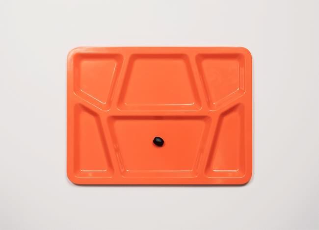 Vemos una bandeja de icopor de   color naranja con una arveja verde en la mitad