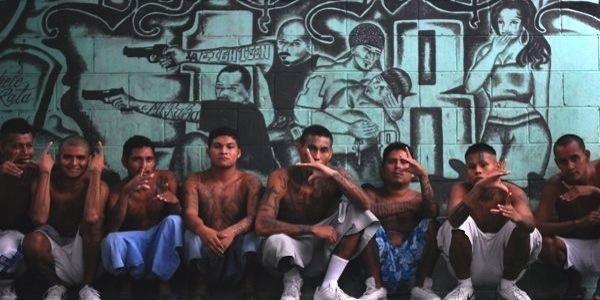 Aqui vemos una cantidad de jóvenes sentados con exprecion feliz que hacen  señas con sus manos atrás se ve un mural que muestra violencia