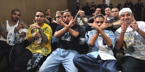 Vemos a un grupo de hombres tatuados y con esposas en sus manos que sonríen y hacen diferentes señas con sus manos