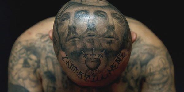 Tenemos una cabeza totalmente tatuada con unos motivos de rostros en su  rostro y cuello tiene  tatuajes