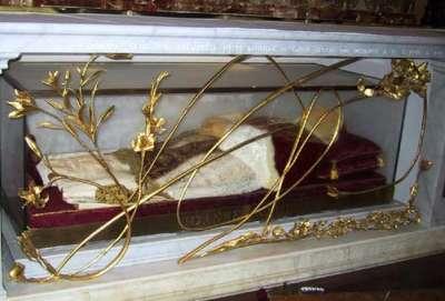 Vemos a un hombre mayor con traje papal que descansa en una urna de vidrio