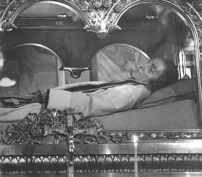 Vemos a un hombre con habito  de sacerdote en un  féretro de vidrio