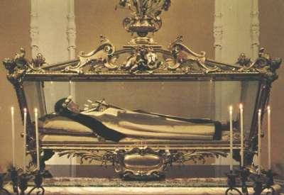 Vemos a una mujer con habito de monja que descansa en un féretro de vidrio sostiene esn sus manos un crucifijo