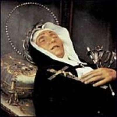 Vemos auna mujer con traje de monja con ujnas flores en sus manos y un crucifijo descansa en una urna de vidrio