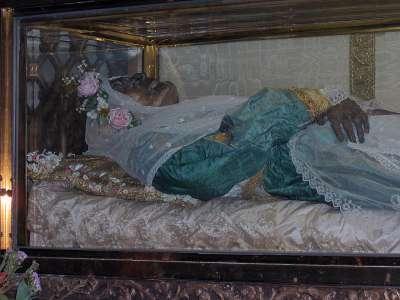 Vemos a una mujer vestida de azul con una corona de flores en la cabeza sus manos descansan una sobre la otra