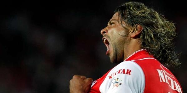 Un futbolista que grita en medio de la cancha lleva su uniforme rojo y blanco
