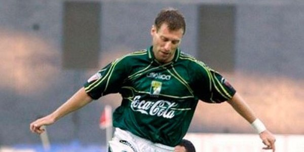 Otro futbolista rubio con uniforme verde y blanco que corre con el balón