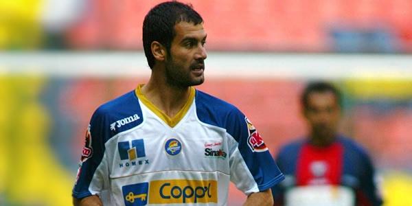 UN futbolista con uniforme blanco con azul con  rostro fuerte avanza por la cancha