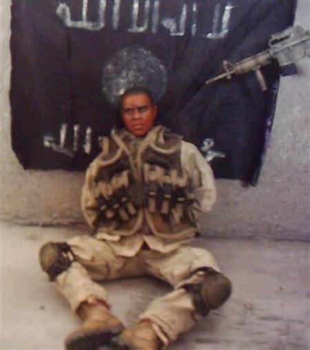 Aquí un soldado negro con su uniforme sentado en el amarradas sus manos  detrás de el una bandera y una arma  que le apunta  a su cabeza