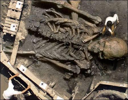 Vemos aun esqueleto humano gigante y un hombre que se acerca a mirar