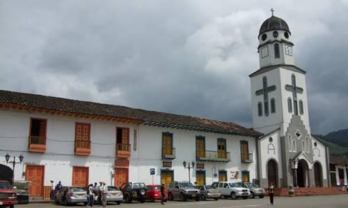 Unas casa antiguas y una iglesia  sobre una calle muy larga en un pueblo muy hermoso