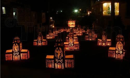 Vemos una  calle oscura en donde se ven muchos faroles encendidos hechos con hermosos motivos navideños