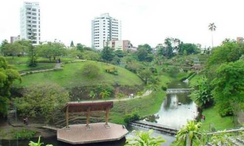 Vemos un parque con lago sendero ecologico muchas partes verdes bancas para sentarse a descasar esta en medio de una parte muy concurrida de la ciudad