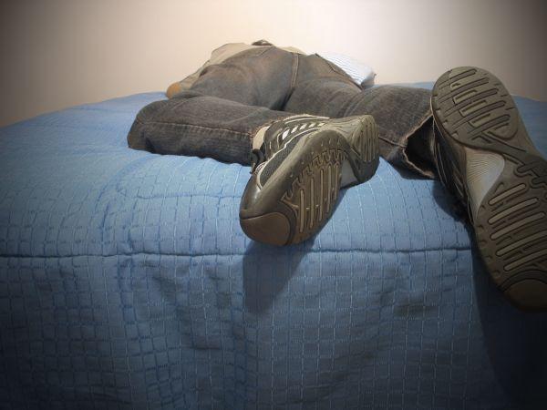 Vemos a una persona acostada en una cama con zapatos