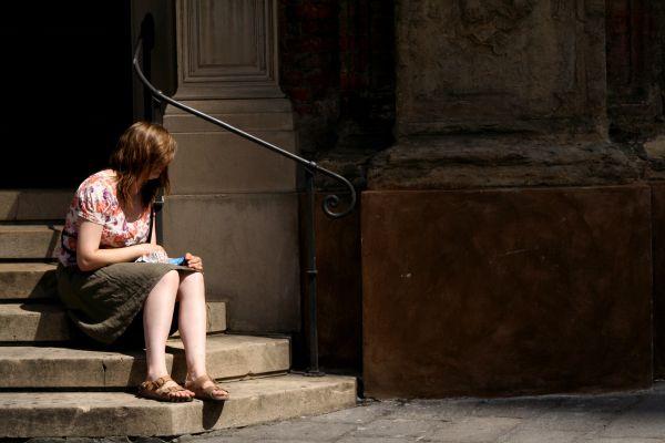 Tenemos  una mujer joven sentada en una escalera con el pelo en la cara