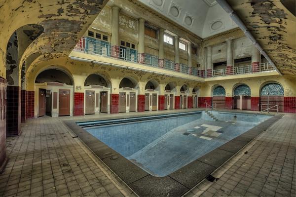 Una piscina en el medio de una propiedad en la cual las paredes estan muy despicadas