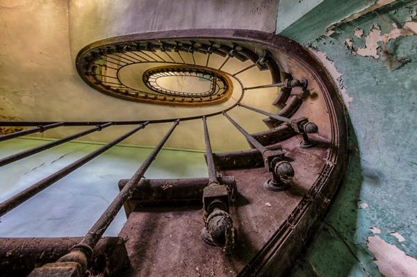 Unas escaleras en caracol muy oxidadas y unas paredes descascaronadas