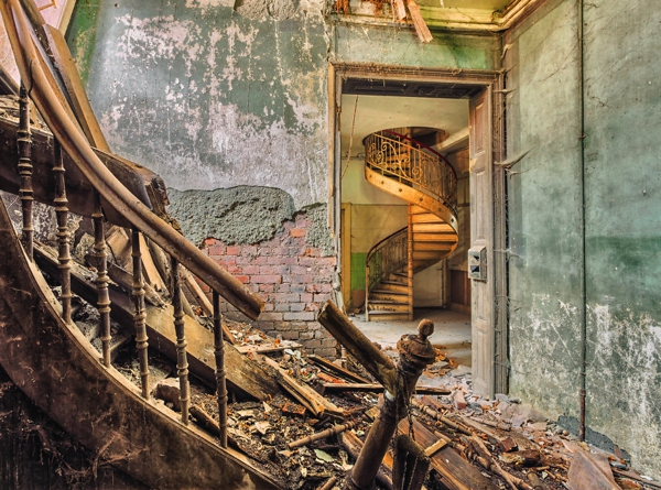 Una habitacion donde hay unas escaleras quebradas y esta el lugar lleno de escombros