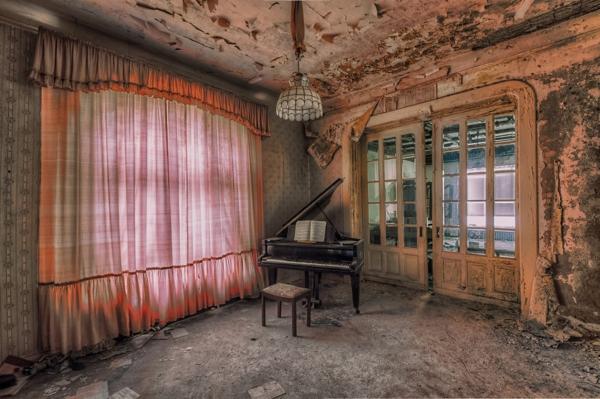 Un cuarto con las paredes derrocadas en el cual hay un piano es una esquina