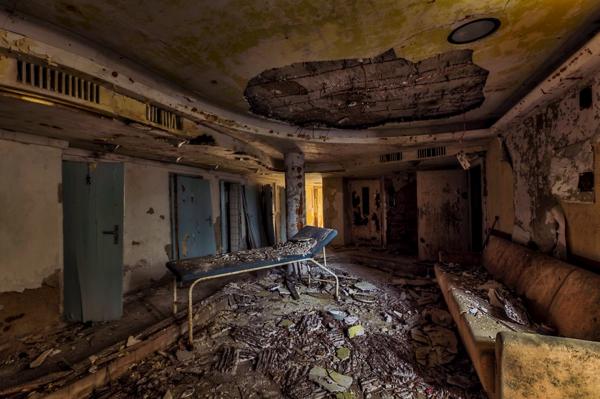 Un cuarto muy feo y lleno de escombros en el cual hay una cama de hospital en el medio