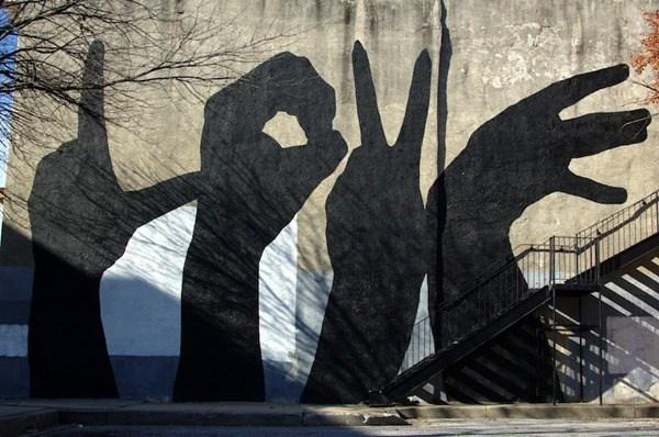 Varias manos negras con diferentes simbolos plasmadas en la pared