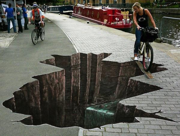 Un hueco profundo en el piso por el cual esta pasando una señora en una bicicleta mediante una tabla