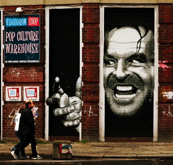 Un mural en el cual por una puerta se ve la cara de un hombre, al lado hay otra puerta y por esta puerta se ve como si estuviera sacando la mano