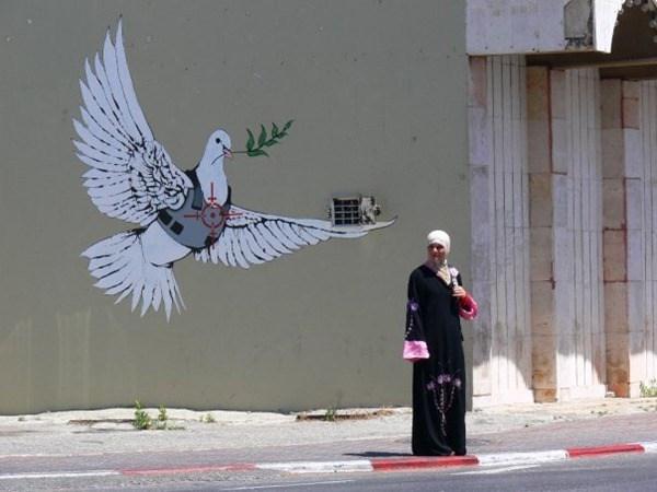 Una paloma con una hoja de olivo en su pico una mujer con hiya observa