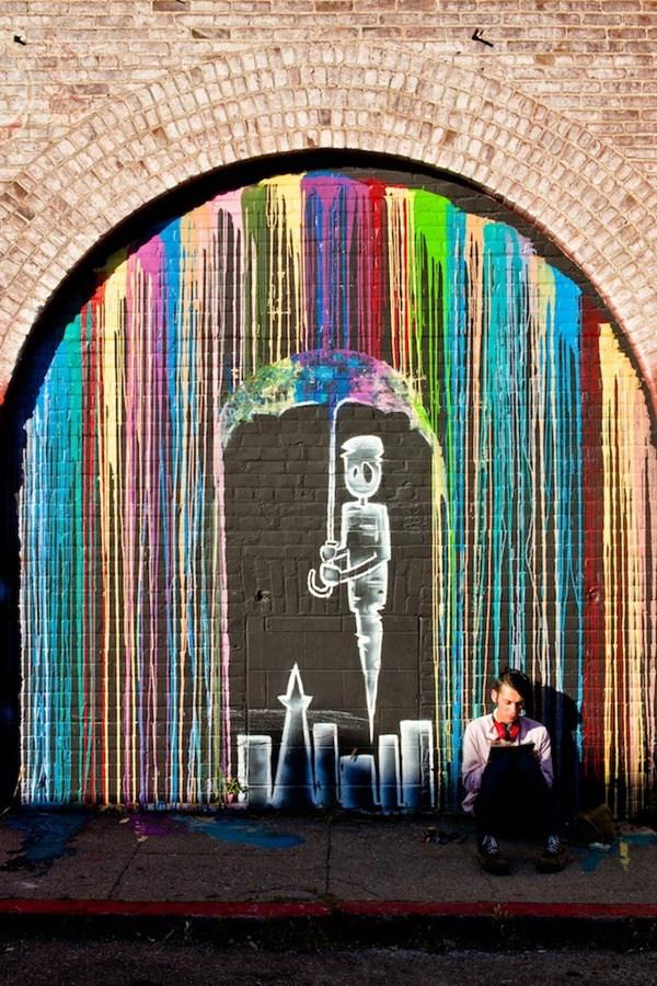 Una lluvia de colores y hay un muñeco con una sombrilla protegiendose de esta lluvia