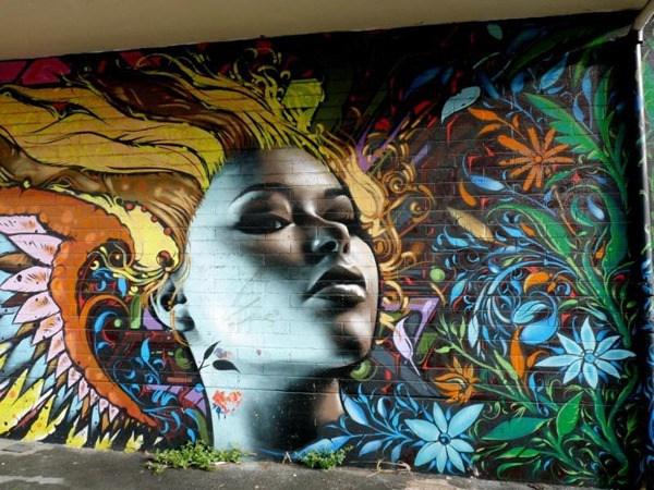 Una mujer con pelo de colores y alrededor de ella flores muy coloridas y otro tipo de cosas abstractas