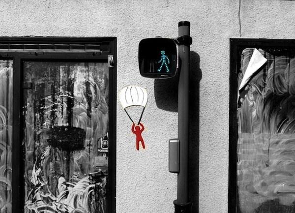 Un semaforo peatonal esta en verde y a un lado afuera del semaforo se ve el muñequito rojo descendiendo con un paracaidas