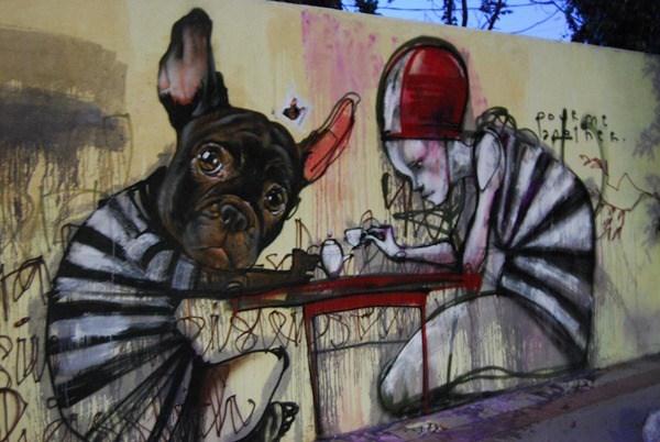 Un perro y un hombre con traje de prisioneros tomando café