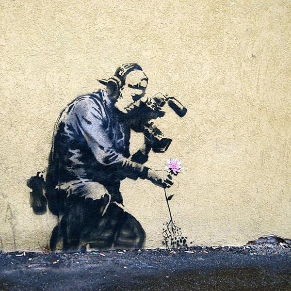 Un hombre arrodillado tomandole una foto a una flor
