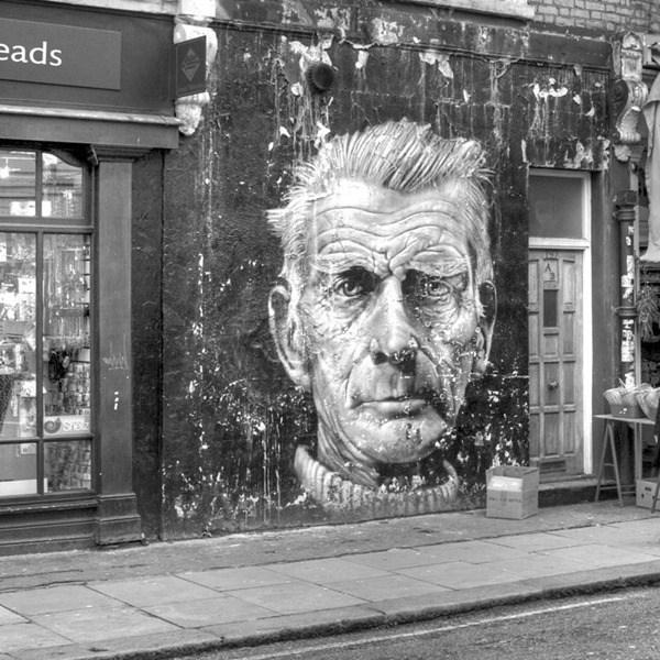 El rostro de un señor de edad plasmado en una pared