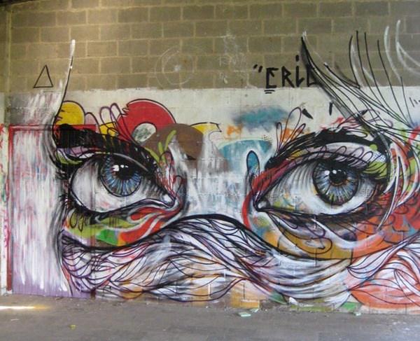 Un rostro en la pared del cual el cabello tapa su nariz su cabello y partes del rostro son de colores