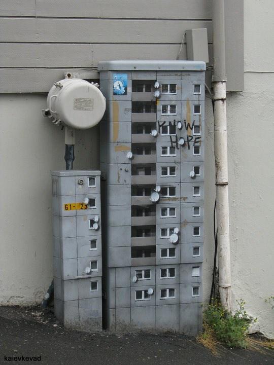 Un edificio plasmado en una puerta de donde sacan conexiones para la electricidad