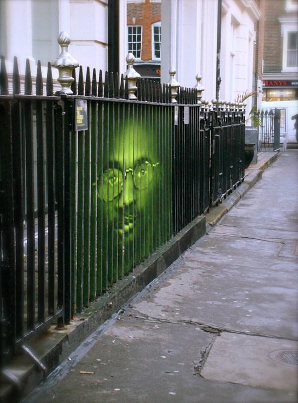 Un hombre dibujado en unas rejas, el hombre esta pintado de color verde y tiene gafas