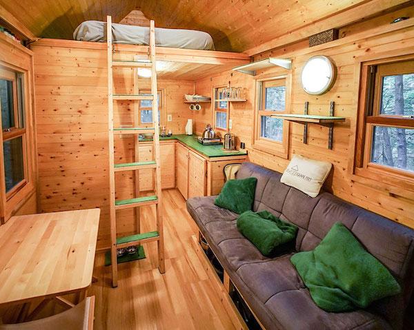 Una casa con su dormitorio en el pico y en la parte de abajo su sala y cocina